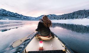 湖泊上划着小舟的美女背影摄影图片