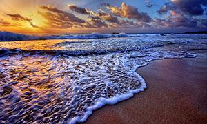 傍晚海邊海浪拍打著沙灘攝影圖片