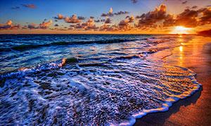 夕陽下的金色沙灘和海浪攝影圖片