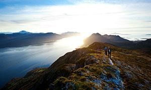 早晨在攀登到山頂的游客攝影圖片