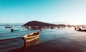 藍天下湖泊中停泊的小船攝影圖片