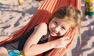 沙灘上在吊床里的小女孩攝影圖片