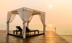 傍晚沙灘上的蚊帳和靠椅攝影圖片