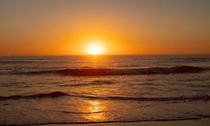 夕陽下海浪拍打著沙灘攝影圖片