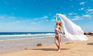 沙灘上拿著網紗的比基尼美女攝影圖片