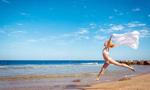 沙灘上舉起綢帶跳起的美女攝影圖片