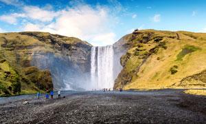 在悬崖下的观看瀑布的游客摄影图片