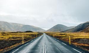 烏云下通向大山的公路攝影圖片