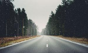 大雪紛飛的山林和公路攝影圖片
