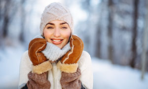冬季帶著帽子微笑的美女攝影圖片