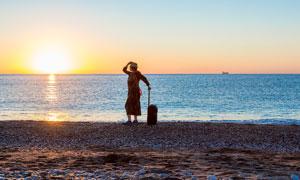 傍晚在海边拉着行李箱的游客摄影图片