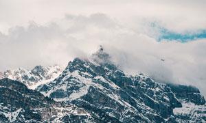 云霧圍繞的雪山景觀攝影圖片