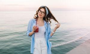 海边端着饮料的长发美女摄影图片