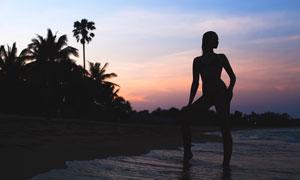 傍晚沙灘上的美女剪影攝影圖片