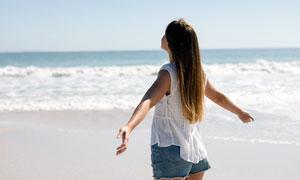 海边拥抱大海的美女背影摄影图片