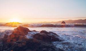 夕陽下的海浪和巖石攝影圖片