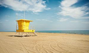 沙灘上的黃色救生站攝影圖片