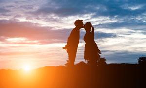 夕陽下的情侶接吻剪影攝影圖片