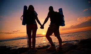 傍晚海邊手拉手的情侶剪影攝影圖片