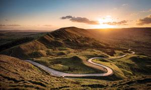 夕阳下弯曲的山路景观摄影图片