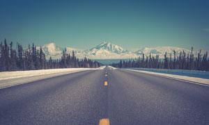蓝天下通向雪山的公路摄影图片