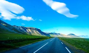 蓝天下的公路和绿色草地摄影图片