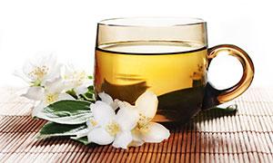 绿叶白花与玻璃杯茶水摄影高清图片