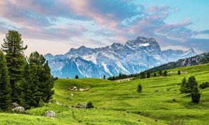 大山中山坡上的綠色草地攝影圖片