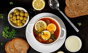 柠檬橄榄全麦面包与一碗汤摄影图片
