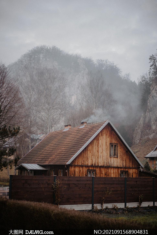 山脚下炊烟袅袅的木屋摄影高清图片