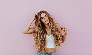 粉色墙壁前的卷发美女摄影高清图片
