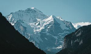 山林植被与积雪覆盖的高山高清图片