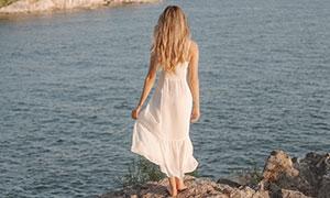 海边岩石上的白裙美女摄影高清图片