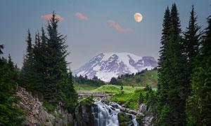 雪山瀑布與高掛空中的明月攝影圖片