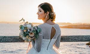 手拿著捧花的白色婚紗美女攝影圖片