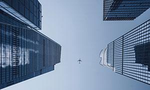 城市建筑与空中的飞机仰拍摄影图片