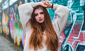 涂鸦墙壁前的长发美女摄影高清图片