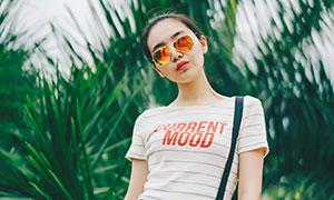 绿叶植物前的墨镜美女摄影高清图片