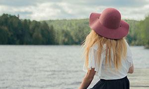 在水边坐着的戴帽长发美女摄影图片
