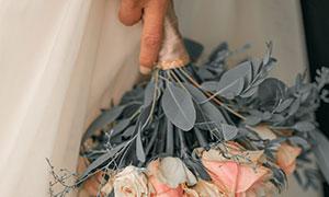 手中的玫瑰与尤加利叶摄影高清图片