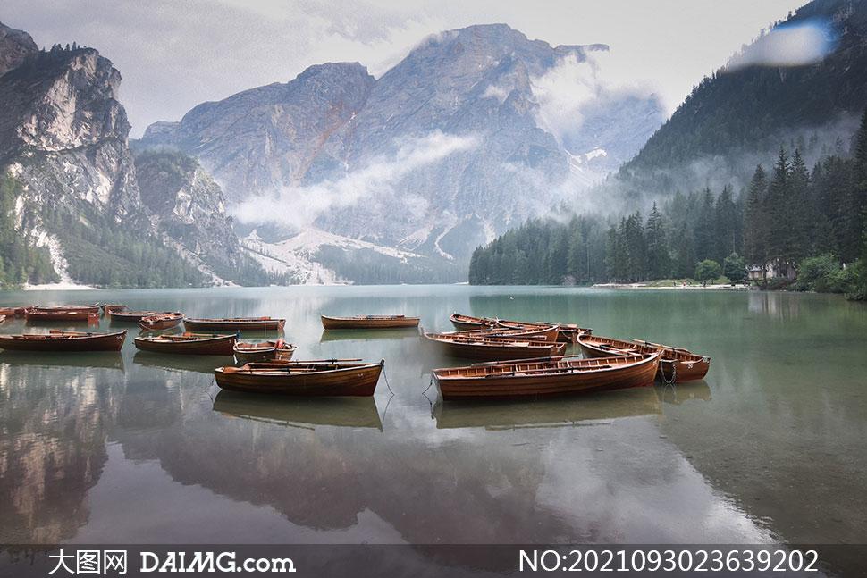高山树林与湖上的船只摄影高清图片